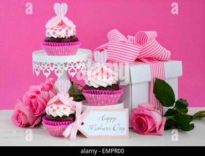 Heureuse Fête des mères rose et blanc cupcakes sur retro style cake stands et boîte-cadeau sur la table de bois Banque D'Images