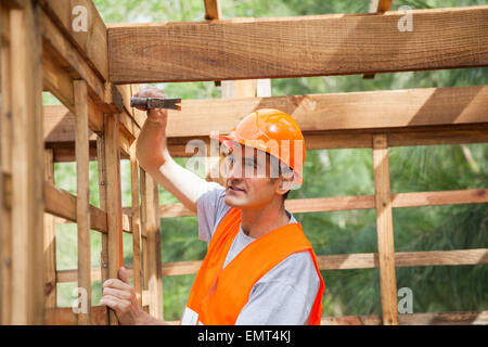 Martelage travailleur clou sur chalet en bois