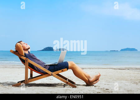 Smiling businessman with computer détente sur la plage Banque D'Images
