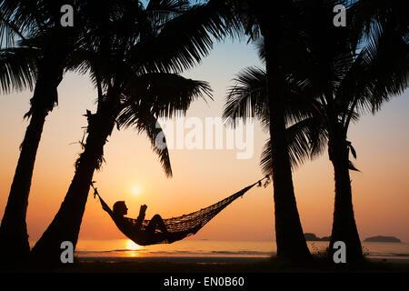 Les vacances à la plage, silhouette of woman reading in hammock Banque D'Images