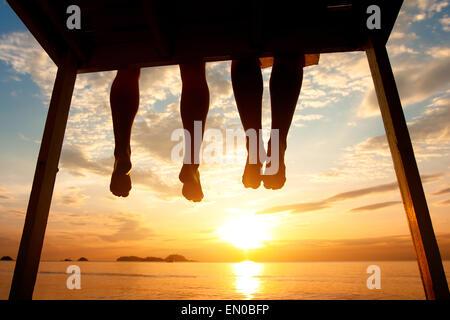 Silhouette de pieds de couple sitting on the pier at sunset beach, low angle view Banque D'Images