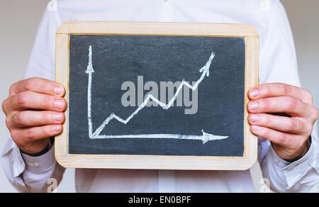 Le développement durable des infographies, business man holding sign on chalkboard Banque D'Images