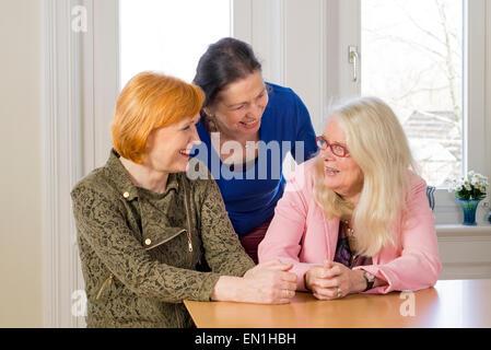 Près de trois femmes d'âge moyen heureux de jouir de leurs amis Girl Talk à la table à manger en bois à l'intérieur Banque D'Images