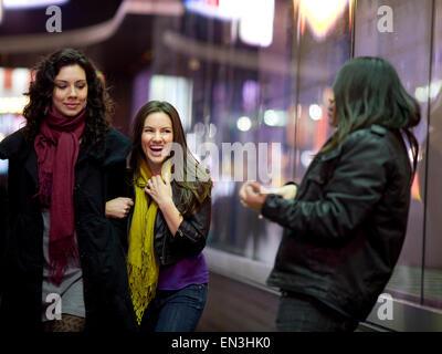 USA, New York City, Manhattan, Times Square, deux jeunes femmes marchant à côté de man window display Banque D'Images