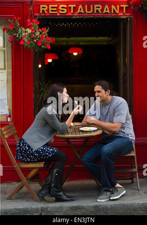 France, Paris, Young couple sitting in sidewalk cafe Banque D'Images