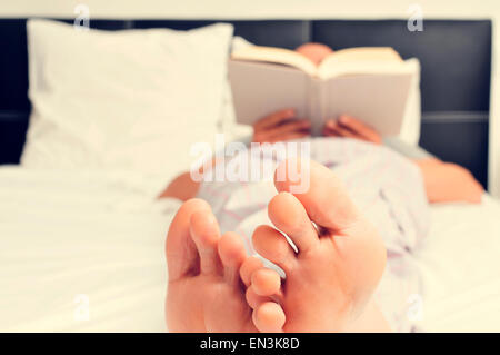 Un jeune homme de race blanche dans les pyjamas pour lire un livre au lit Banque D'Images