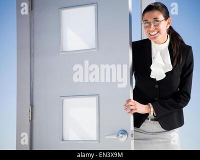 Businesswoman sortant d'une porte dans le milieu de nulle part Banque D'Images