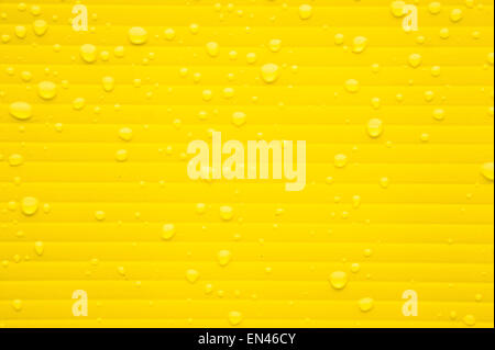 Gouttes d'eau de pluie sur une surface en plastique jaune Banque D'Images