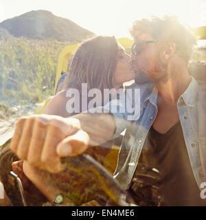 Jeune couple s'embrasser dans la voiture. Couple in love on road trip s'amusant. Banque D'Images