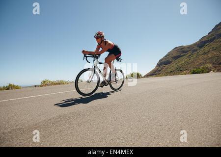 Image de jeune femme à vélo sur la route de campagne. Athlète féminine monter à cheval en bas de la colline à vélo. Banque D'Images