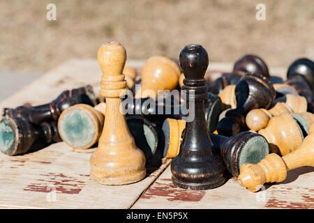 Vieux et flétri des rois se font face sur un vieux jeu d'échecs. D'autres pièces des échecs de mise en pile derrière d'eux.