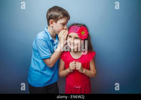 Adolescent garçon d'apparence européenne dans une chemise bleu cheveux brun chuchote à l'oreille un secret girl Banque D'Images