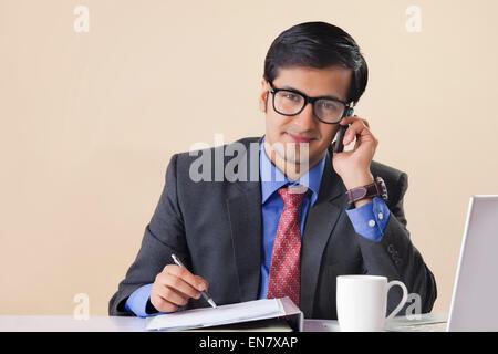 Businessman talking on mobile phone et prendre des notes au bureau Banque D'Images