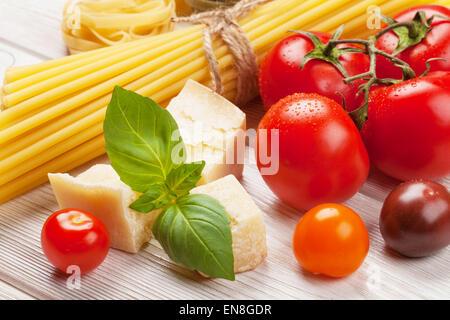 Ingrédients de cuisine italienne. Les pâtes, les tomates, le basilic sur table en bois Banque D'Images