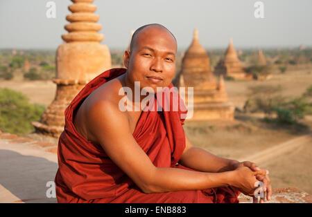 Portrait d'un moine bouddhiste assis sur le dessus d'un temple avec une ligne de flèches à l'arrière-plan du temple Banque D'Images