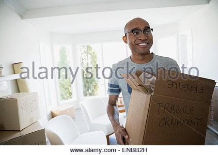 Smiling man carrying case déménagement fragile Banque D'Images