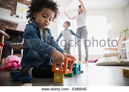 Fille jouant avec des blocs sur le plancher du salon Banque D'Images