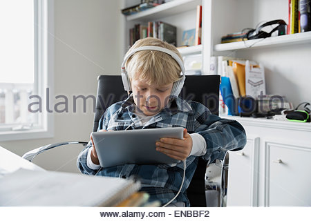 Boy wearing headphones and using digital tablet Banque D'Images