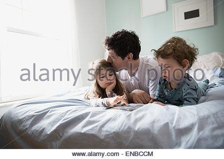 Le père et les enfants using digital tablet in bed Banque D'Images