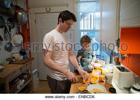 Père et fils couper les oranges pour le petit-déjeuner cuisine Banque D'Images