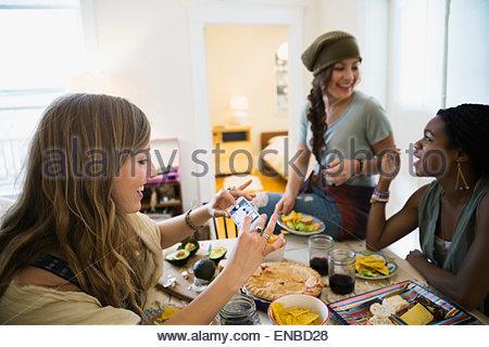 Photographier une femme avec des aliments téléphone appareil photo table à manger Banque D'Images
