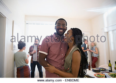 Laughing couple hugging at dinner party Banque D'Images