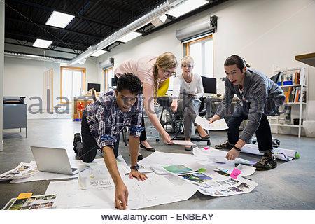 Les concepteurs graphiques réunion l'examen d'épreuves sur plancher de bureau Banque D'Images