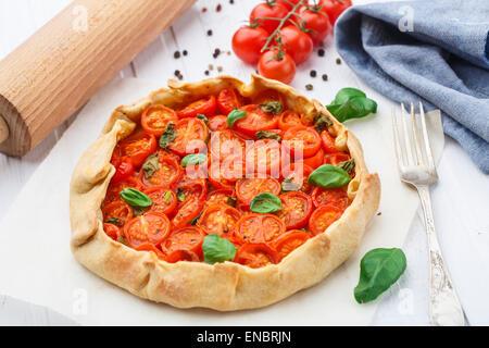 Tarte aux tomates cerises au basilic sur un papier parchemin Banque D'Images