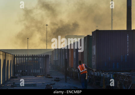 Un travailleur sur le terminal à conteneurs du port de Walvis Bay, en Namibie, à côté d'un train de marchandises Banque D'Images