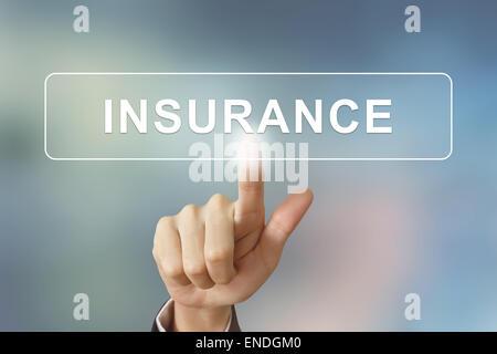 La main d'affaires d'assurance en poussant sur le bouton Arrière-plan flou Banque D'Images