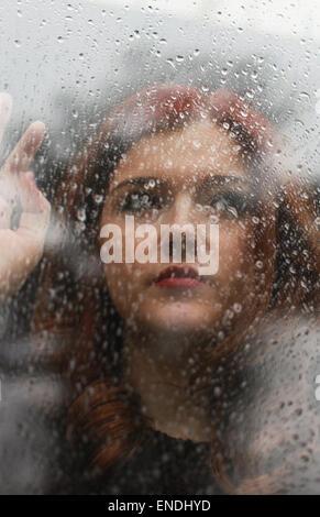 Jolie fille à la recherche d'une fenêtre qui est couvert de gouttes de pluie Banque D'Images