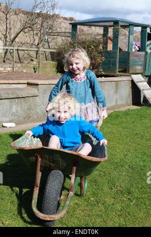 Frère et sœur jouant avec une brouette dans leur jardin Banque D'Images
