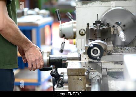 Homme ouvrier faisant le travail manuel avec un tour, une machine industrielle outil utilisé dans le travail des Banque D'Images