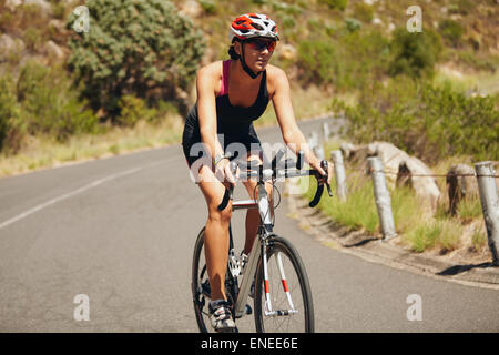 Jeune femme athlète de triathlon vélo. Athlète féminine du Caucase équitation randonnée sur route de campagne. Banque D'Images