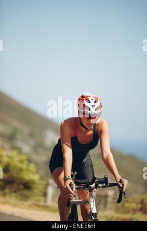 Jeune femme athlète vélo sur route de campagne. Woman riding bicycle pour pratiquer la compétition de triathlon. Banque D'Images