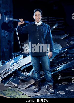 Portrait d'un homme, travailleur de la construction, avec une masse en un tas de gravats de démolition Banque D'Images