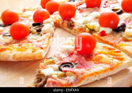 Quelques tranches de pizza au bacon, olives, tomates cerise, fromage de chèvre, poivrons et aubergines Banque D'Images
