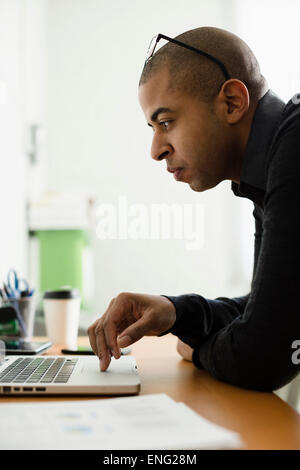 Mixed Race businessman working on laptop at desk Banque D'Images