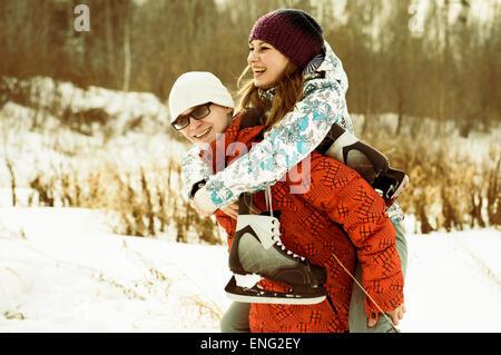 Couple portant des patins à glace in snowy field Banque D'Images