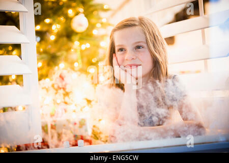 Caucasian girl peering out window à Noël