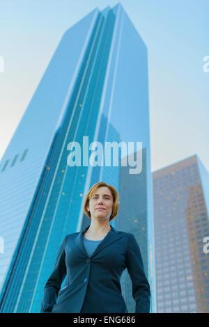 Low angle view of Caucasian businesswoman sous les immeubles de grande hauteur Banque D'Images