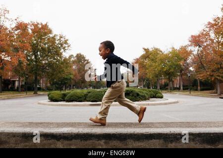 African American boy jouant sur la rue de banlieue Banque D'Images