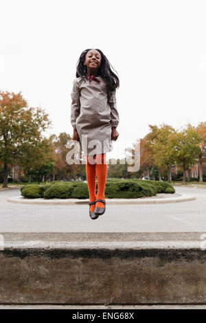 African American girl jumping on Rue de banlieue Banque D'Images