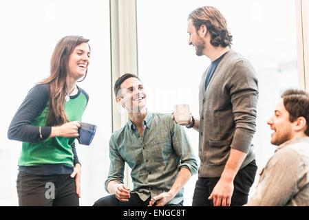 Quatre collègues de travail en pause, rire ensemble. Banque D'Images