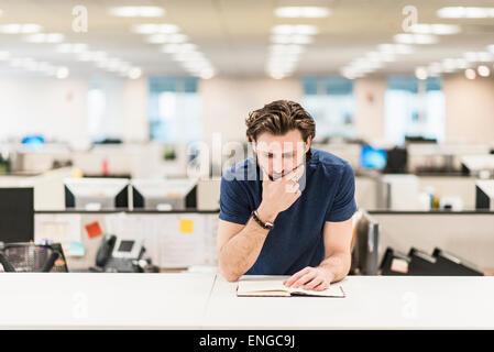 Un homme s'appuyant sur son coude et regardant un livre ouvert sur un bureau. Banque D'Images