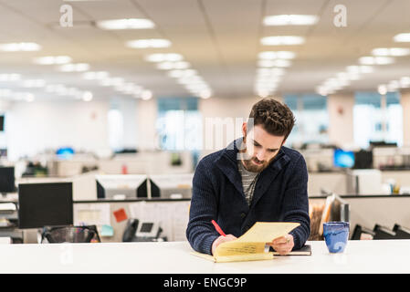 Un homme assis à un bureau dans un bureau écrit avec un stylo rouge. Banque D'Images