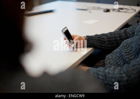 Un homme assis à une table dans un bureau à l'aide de son téléphone intelligent. Banque D'Images