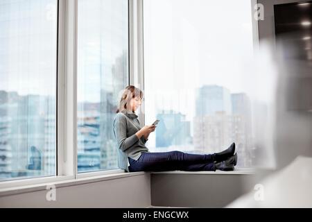 Une femme tenant un téléphone intelligent, assis sur un rebord de fenêtre. Banque D'Images