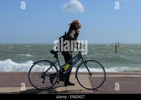 Un cycliste a du mal à faire son chemin le long de la promenade de Southsea à Portsmouth, Hampshire, Angleterre Banque D'Images