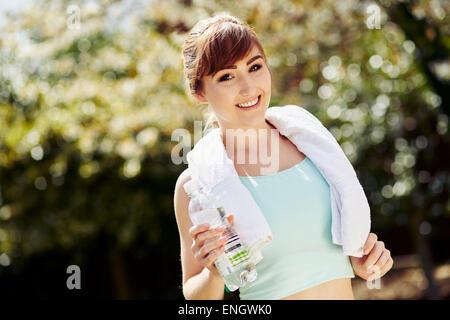 Belle jeune fille tenant une bouteille d'eau après l'entraînement